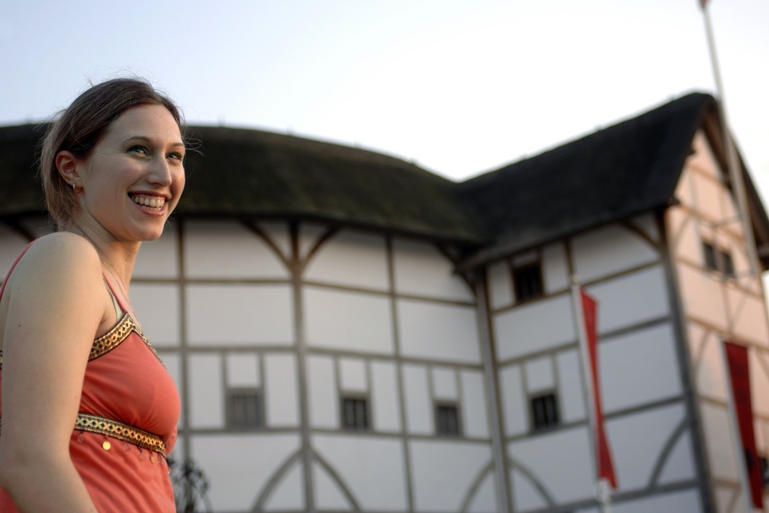 Lady in red top smiling outside the Globe Theatre, London