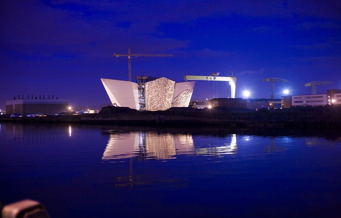 The Titanic memorial in Belfast harbour, lit up against the night sky. Image credited to @nitb.com.