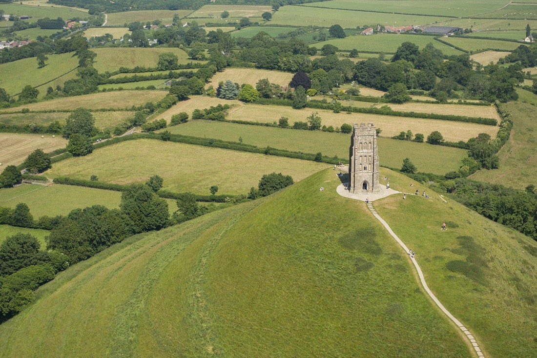 Glastonbury Tor is a hill and national landmark, a natural feature in the landscape, with a tall building, St Michael's Tower on the top. The site is managed by the National Trust. It has been designated as a Scheduled Ancient Monument. Aerial view. ©VisitBritain/ Jason Hawkes