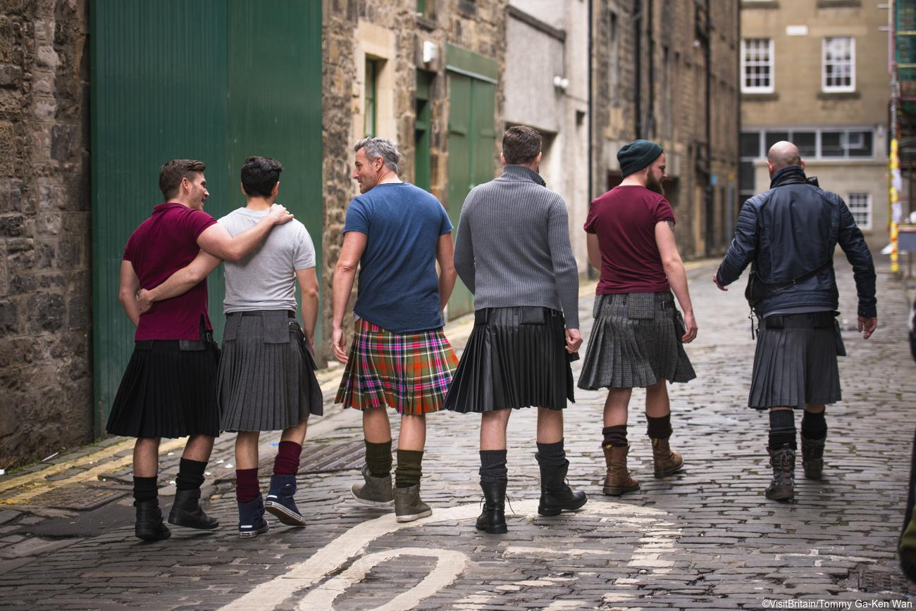 Rear view of group of men wearing kilts walking arm in arm along Thistle Street, Edinburgh, Scotland.