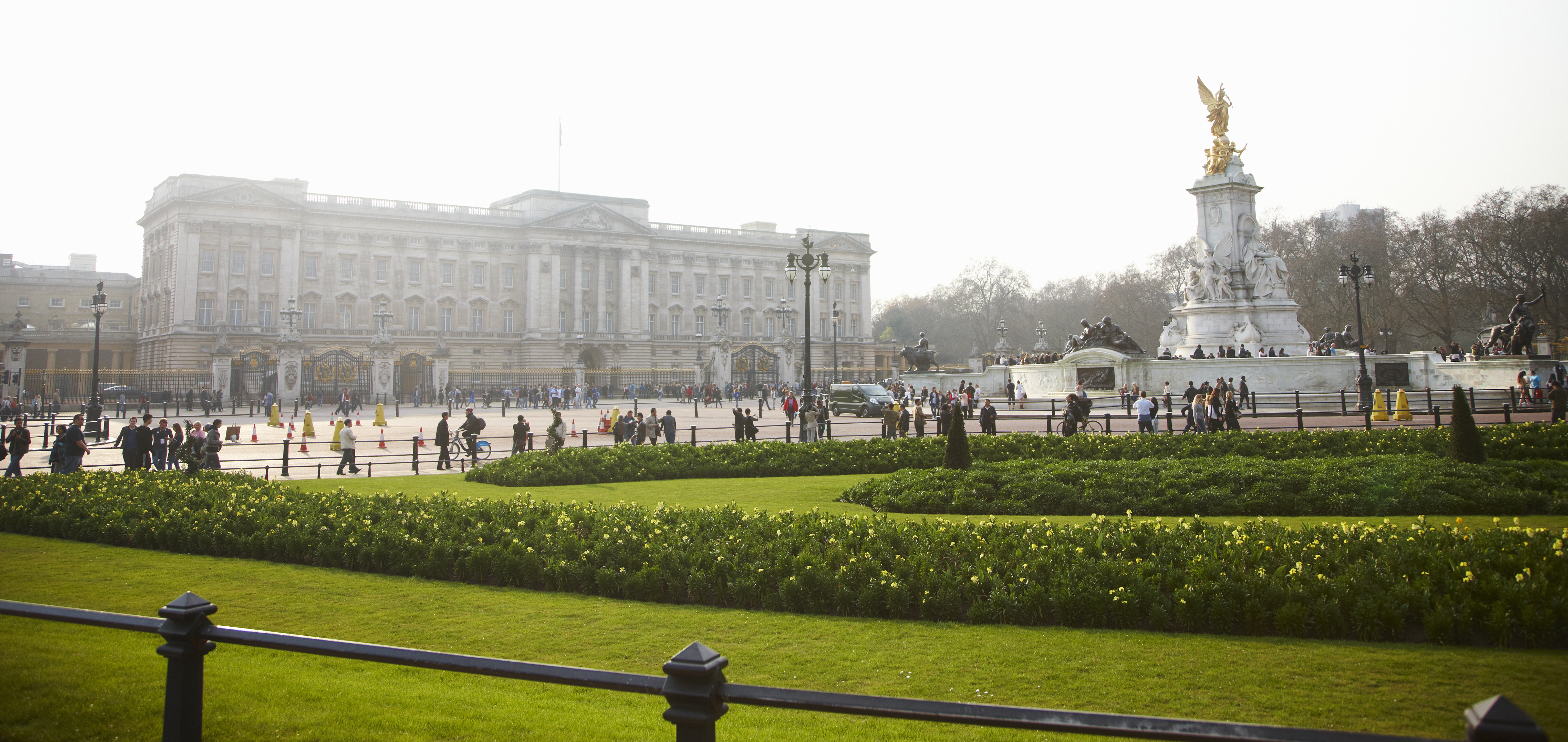 Buckingham Palace in the Mall. The royal residence of the Queen. Queen Victoria memorial at the centre of the traffic flow. Taxis and cars. Bicycles.