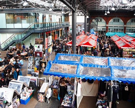 Spitalfields market in East London. Market life, traders and stalls. View over the stalls and aisles and crowds of people in the covered market.