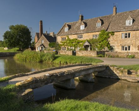 Traditional Cotswold stone cottages and stone footbridge in the Cotswolds village of Lower Slaughter.