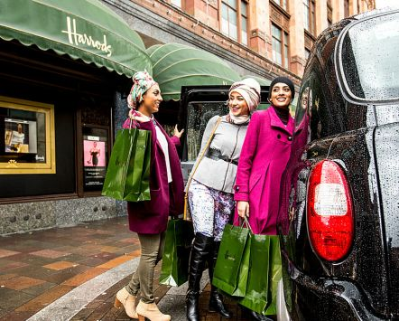 Harrods Department Store, Three young Arabic women getting into a taxi holding Harrod's shopping bags.. A London landmark and well known luxury goods store.
