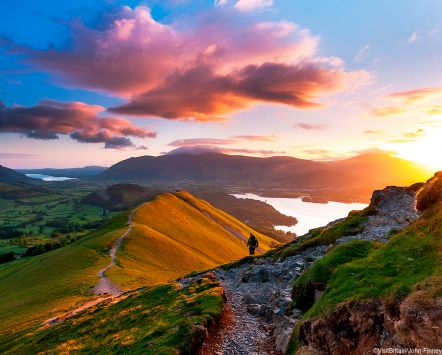 Sunrise on Catbells Mountain, The Lake District, Cumbria, England. Hiker walking along a path on the mountain ridge.
