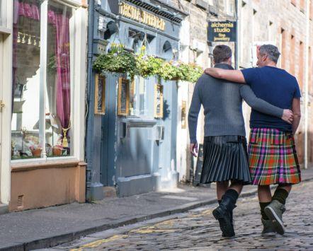 Same sex male couple wearing kilts walking arm in arm along Thistle Street, Edinburgh, Scotland.