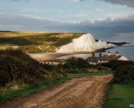 Country road leading towards Coastguard Cottages in Seaford, East Sussex, with white cliffs in the background.