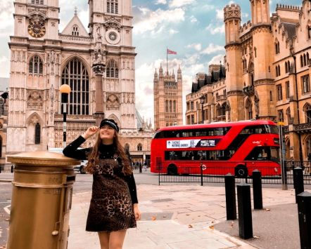 Red bus whizzes past the historic Westminster Abbey in the heart of London, credit to VisitBritain