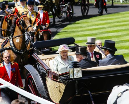 Royal Ascot Race Meeting at the prestigious Ascot racecourse in Berkshire. Royal Procession. Arrival of members of the Royal Family. Queen Elizabeth II and Prince Philip sitting in a horse-drawn carriage with two men. Accompanied by men wearing military u