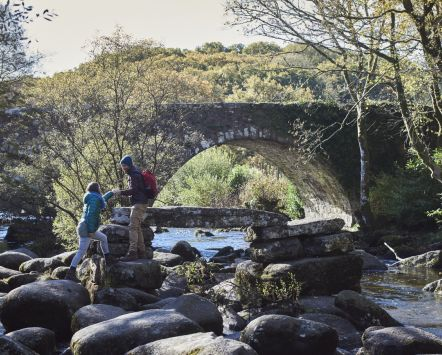 Couple climbing on boulders by a stream, Dartmoor National Park, Devon, England.