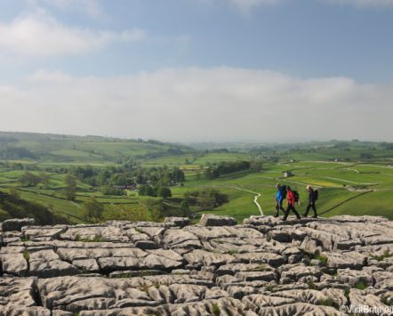 People walking on the limestone pavement above the cliffs of Malham Cove in the Yorkshire Dales. Pennine Way walking route. Hiking. Hikers, walkers.