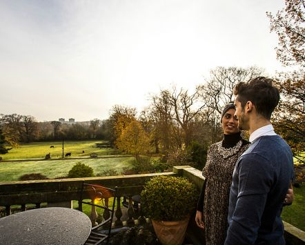 Prestonfield House is a luxurious five star boutique hotel in Edinburgh. An Arabic couple, man and woman, on the terrace looking out over the gardens.
