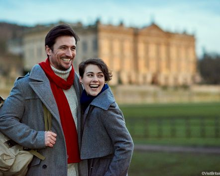 A couple, man and woman, visiting Chatsworth House, a stately home, in the Peak District. Standing close together in half embrace. Blurred view of Chatsworth House and grand estate in the background.