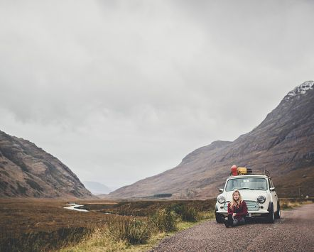 Woman sitting in front of vintage car parked on rural road in Scotland.