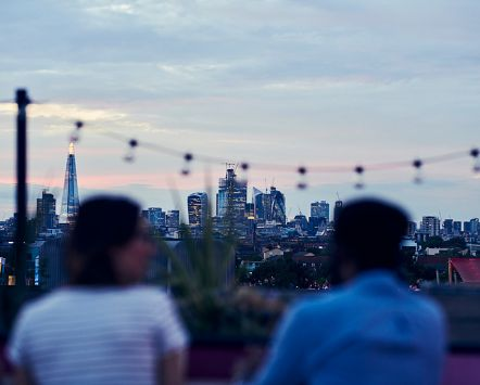 People sitting outside in the evening at Bussey Building Rooftop Bar, Peckham, London, with the London skyline in the distance.