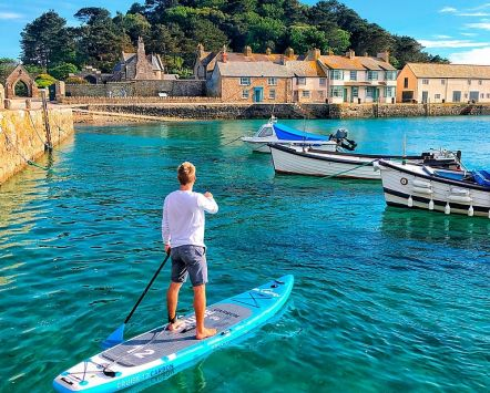 A man paddleboarding at St Michael's Mount, Marazion, Cornwall, England