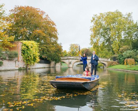 Three people, two women and a man, punting on the River Cam in autumn, Cambridge, Cambridgeshire, England.