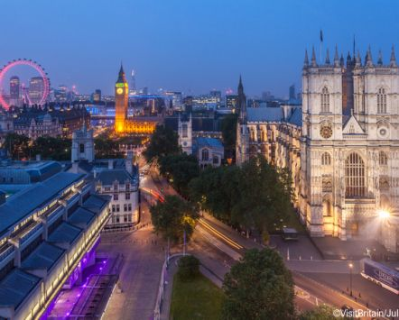 London landmarks, Big Ben clock tower and the Houses of Parliament, view from above at dusk. Westminster Abbey and the River Thames. The London Eye in the background.