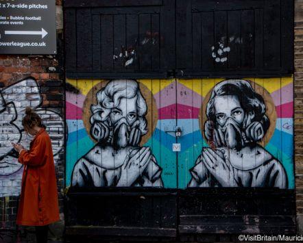 Woman walking past street art on Brick Lane, London, England.