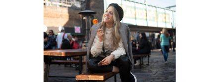 A woman sitting on a bench smiling in Camden Market, London, England. Credit to ©VisitBritain/ Martina Bogglian
