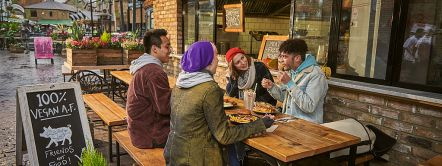 Four friends, two young women and two young men, eating a meal outside a vegan restaurant in Camden, London, UK.