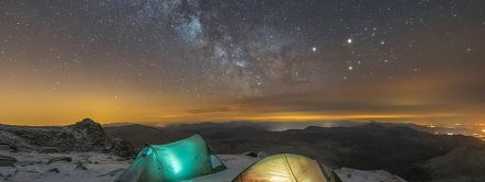 Wild camping on Glyder Fach summit. Two tents with lights inside. Snow on the ground. The Milky Way in the sky, Snowdonia, Wales.