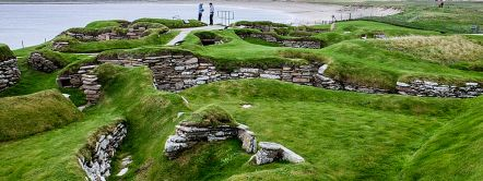 One of Britain's archaeological highlights, Skara Brae neolithic village, coastline and bay. Credit to VisitBritain©Becki Enright