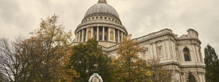 Young man standing on low stone wall and looking up at St Pauls Cathedral, City of London. Credit to VisitBritain/Sam Barker