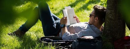 Man reading a book, leaning against a tree at the Hay Festival, Wales.