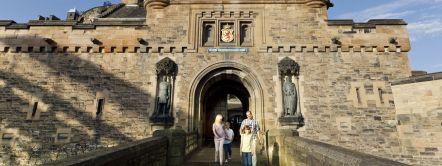A day out in Edinburgh. Edinburgh castle, a historic stronghold on Castle Rock, dominating the city. A family outing, two adults and two children exploring the castle. The gatelodge and entrance walkway.