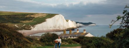 Woman pushing her bicycle up a country road with Coastguard Cottages and white cliffs in the background, Seaford, East Sussex.