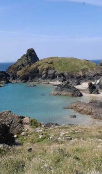 View of Kynance Cove, Cornwall. Walkers in foreground make their way towards the cove.