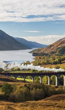 View over Glenfinnan valley with steam train on viaduct and Loch Shiel in the background, Highlands, Scotland.