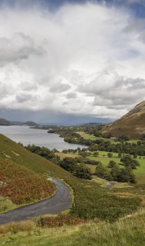 Landscape view with hills and country road under a cloudy sky, a lake in the distance, Ullswater, Lake District, Cumbria.