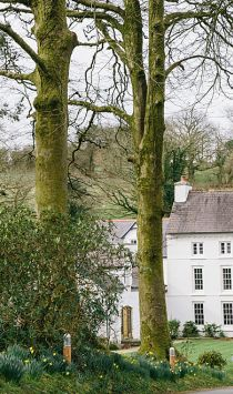 A couple walking and embracing in the grounds of a small hotel in Pembrokeshire, Wales. Love Is GREAT.
