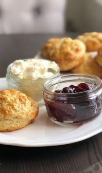 Afternoon tea with scones, milk, clotted cream and jam.