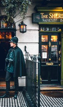 A man in an old style police uniform standing outside the Sherlock Holmes Museum.