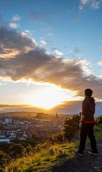 Vue des falaises de Salisbury au coucher du soleil. Jeune homme debout sur un sentier le long des falaises au sommet d'Arthur's Seat, surplombant Edimbourg.