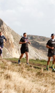 Runners on the Jurassic coast clifftop, cliffs and English Channel in the back ground.