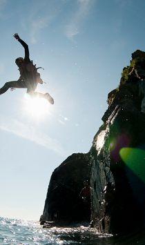 Coasteering, a person jumping into the sea at Mullion Cove, Cornwall, England.
