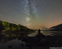 A man sitting on a rock stargazing at Snowdonia International Dark Sky Reserve, Wales. Credit to VisitBritain/Kris Williams