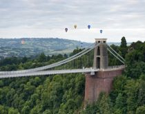 Hot air balloons rising and floating in the air against a cloudy sky, above the city of Bristol and the Clifton Suspension Bridge during the Bristol Balloon Fiesta. River Avon.