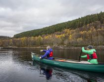 Two people in a Canadaian canoe on the waters of Loch Beina a Mheadhoin in Glen Affric.