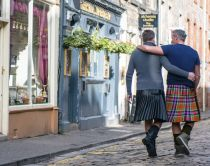 Same sex male couple wearing kilts walking arm in arm along Thistle Street, Edinburgh, Scotland.