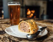 Beer and plate with sausage role