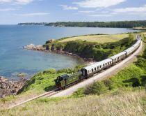 Steam train on the Dartmouth Steam Railway line, approaching Churston running along the coastline © VisitBritain / David Clapp