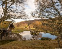 Eagle Brae, luxury self-catering log cabins, eco lodges powered by renewable energy. Small buildings in an open space, around a lake.