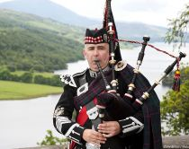 A highland piper playing the bagpipes. Standing in traditional Scottish piper's uniform on top of rock formation overlooking river and green rolling hills and landscape in Perthshire, Scotland.