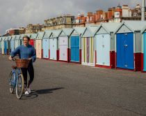 Woman pushing her bicycle past colourful beach huts on Hove Lawns Seafront, Brighton, East Sussex.