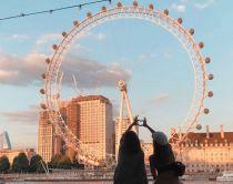 Meisjes maken hart met handen voor de London Eye